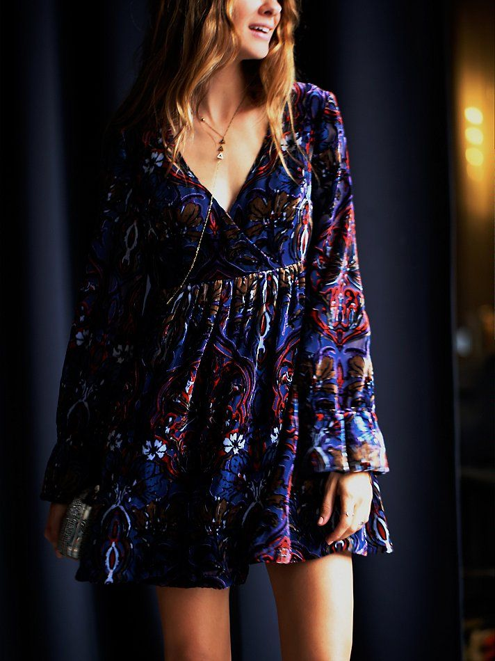 Mystic Charm Dress   Printed babydoll style velvet dress featuring a surplice bodice with a V-neckline.  Long sleeves with a statement cuff and pleat detailing along the skirt.  Lined.