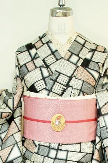 生成り色とグレーと黒のモノトーンに優しいピンクが差し入れられ、外国の積み木の玩具を思わせるモダンデザインが織り出された銘仙袷着物です。