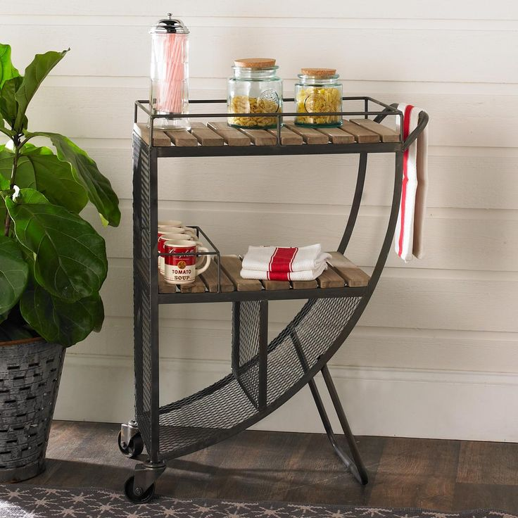 """Quarter Circle Rustic Bar Cart An attractive twist on a classic design makes this rustic iron bar cart as stylish as it is practical. Two front wheels make it easy to move around. The bottom racks are great for storing wine bottles and the two shelves are perfect for glasses and mixers. (36.5""""Hx26.5""""Lx14""""W)."""