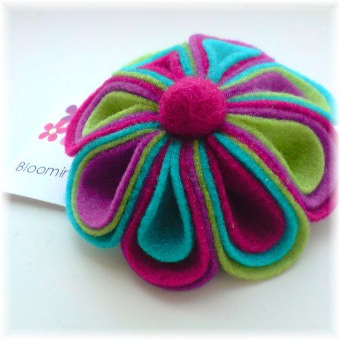 This brooch has been made from four different colours of vibrant felt which has been crafted into 8 individual petals - each of which feature three different colours! It has been decorated with a contrasting felt ball.