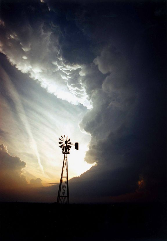 A lone windmill stands against a supercell storm in Leedey, Okla.