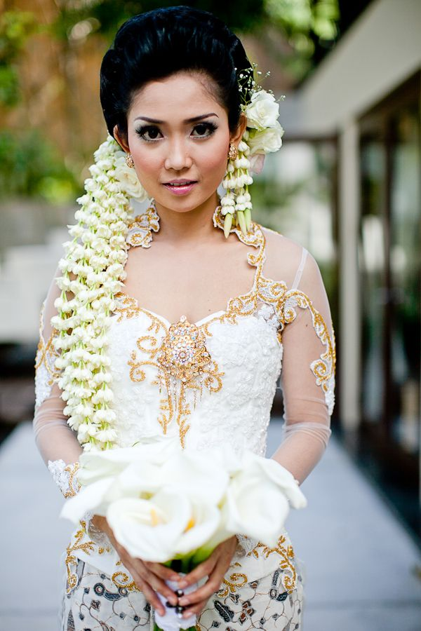 bride in Indonesian wedding garb with lily bouquet - traditional Indonesian wedding in Bali - photo by Portland wedding photographer Bunn Salarzon