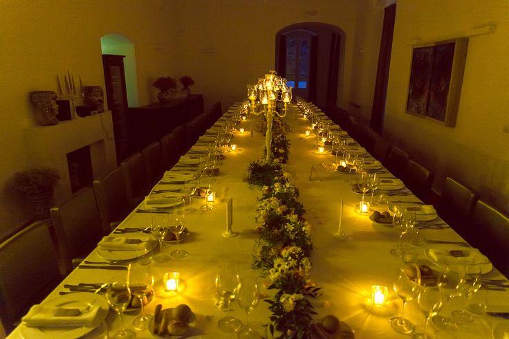 Wedding dinner, imperial table.Fresh flowers runner and white chandeliers.