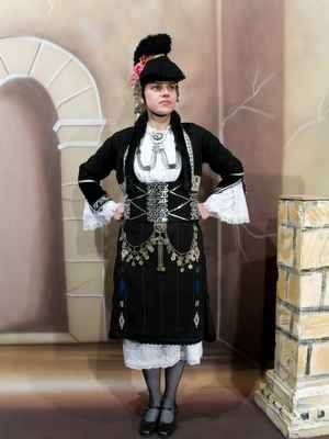 Macedonian female costume is one of the heaviest. The fabric was really thick to protect in winter and black to be imposing. You can also see the traditional helmet that looks like ancient roman. It is full of ornaments, flowers and golden coins.