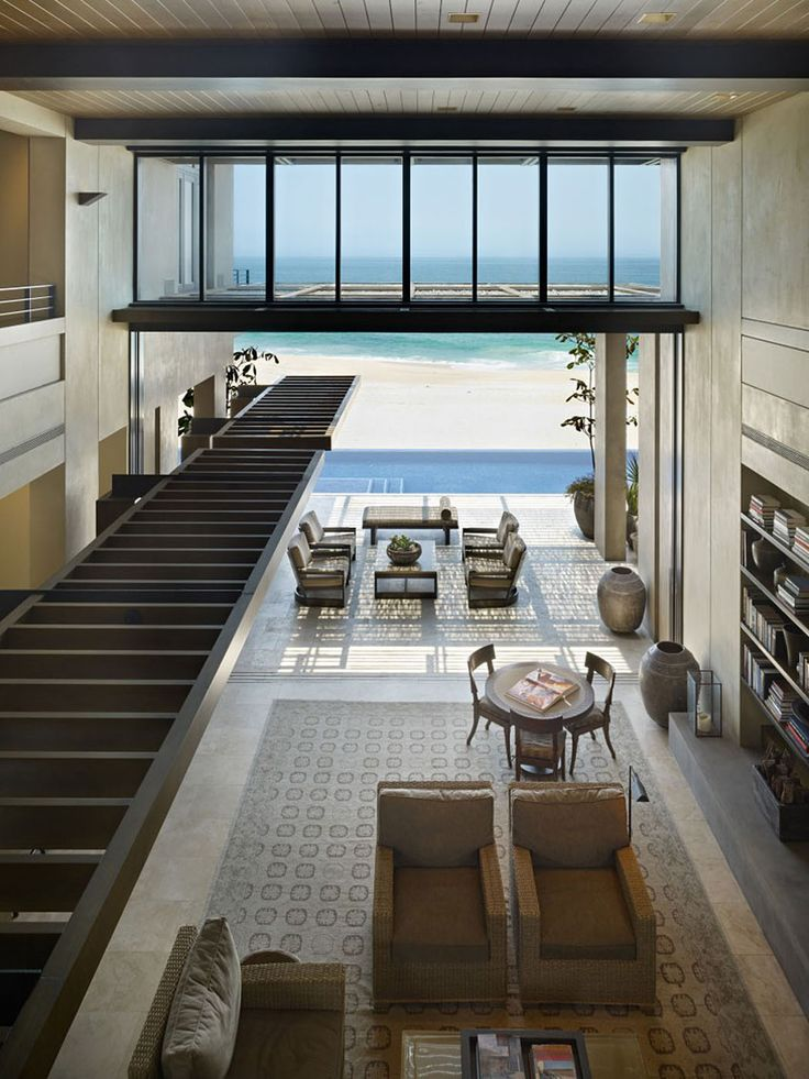 Le premier niveau où se trouvent le séjour, la cuisine, la salle à manger sur un fond de sable blanc et mer turquoise