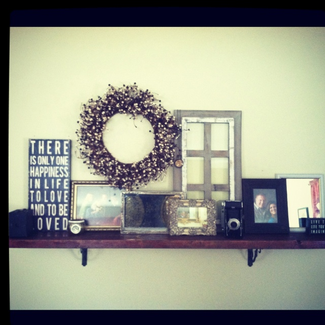 DIY shelf / mantle for livingroom: one 2x10x5 wooden board, stain, wrought iron shelf holders, black screws, pictures mirrors wreaths and things you love