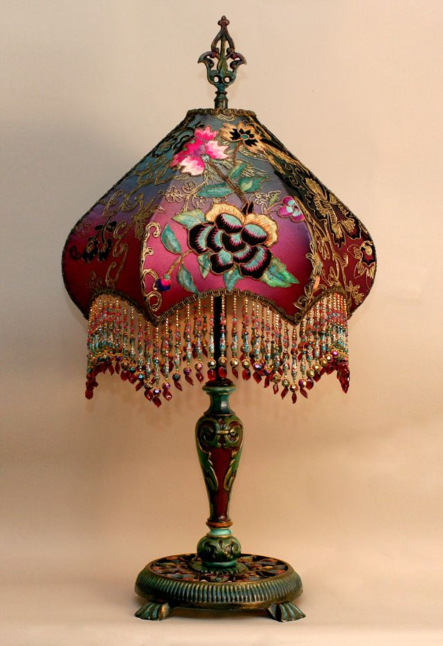 A highly detailed, hand-painted antique lamp base holds a hand-dyed Fuschia Peony & Butterfly silk lampshade. The shade is ombre-dyed from deep teal to fuschia and covered with brilliantly colored antique Asian flowering vine appliques, as well as a multilolored butterfly. The shade is covered in a rich gold and black net and then overlaidwith the floraal motifs. The colors of the lamp are intense and beautiful. The shade has hand beaded fringe in matchingtones.