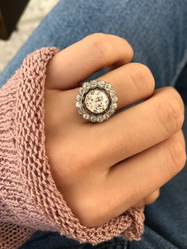 The Maisie ring is an early Edwardian ring circa 1910! This extraordinary beauty centers an old European cut diamond weighing approximately 2.10 carats of H-I color, SI1 clarity. The diamond is held in a platinum bezel setting which is surrounded by delicate and lacy filigree that is then encased by a halo of 16 old cut diamonds that combine for a total of 1.12 carats. To each side of the cluster is an additional diamond set in platinum atop a 14 kt yellow gold band.
