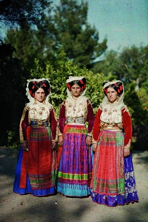 Corfu, Greece. This headdress is made with the hair itself with red ribbons, white lace scarf, and sometimes added flowers and feathers for decoration.