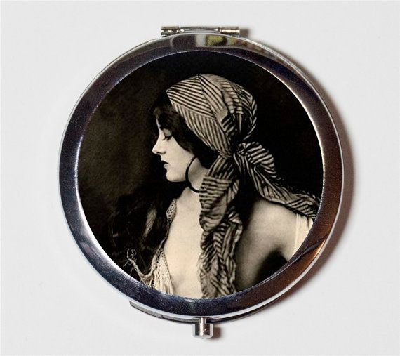 This brand new compact mirror was handcrafted and designed by me, Astrid Daley, in my Seattle studio. The pocket compact mirror features a 1920s era image of a Ziegfeld Follies flapper with a decidedly bohemian appearance.  The first picture is of the item you will receive. The other pictures are examples of what my finished mirrors look like.  Mirror Details: ● 2 and 3/4 inches size ● Silver-tone finish ● Two mirrors inside-- one is regular, the other magnified! ● Push button to open and…