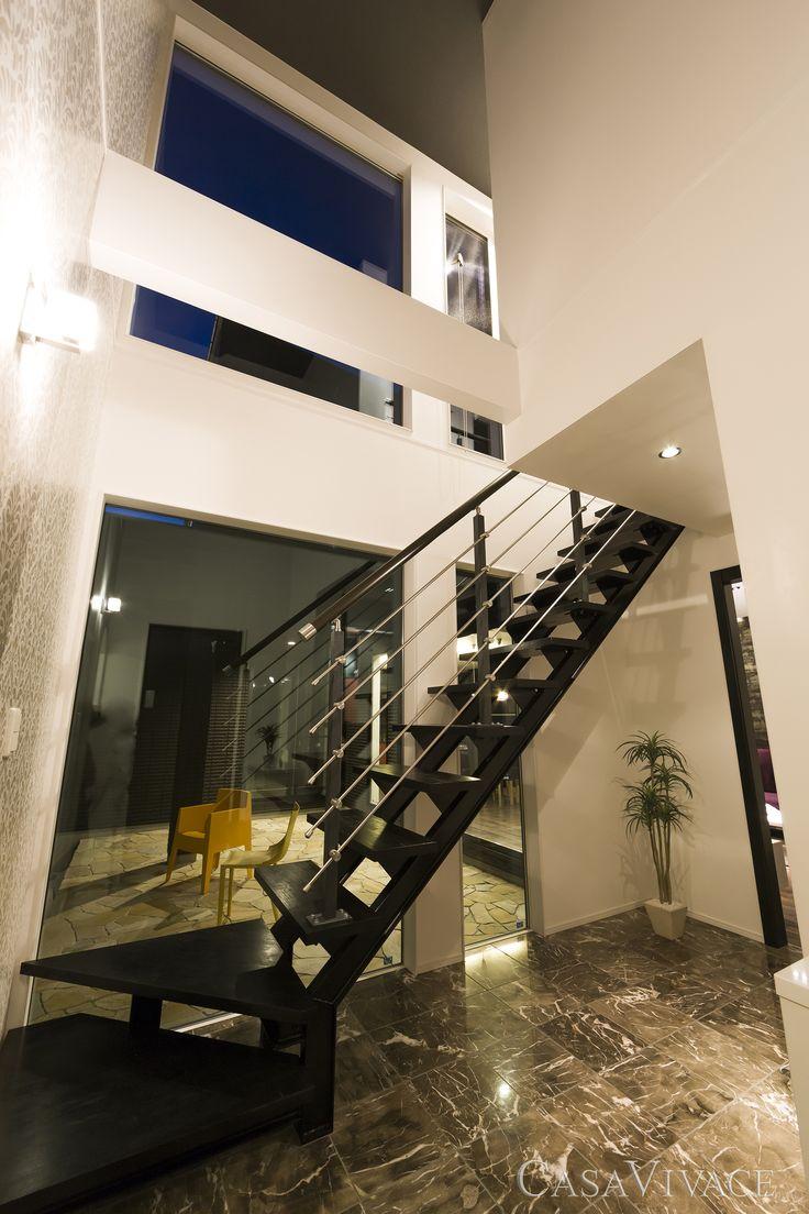 クレモナタイルパティオのある黒い外観のモダンハウス