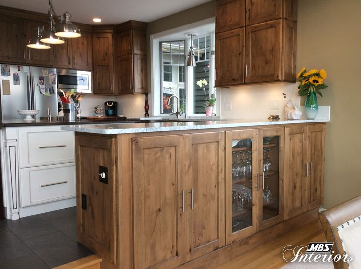 A kitchen in charlevoix michigan is effortlessly rustic - Off white cabinets with chocolate glaze ...