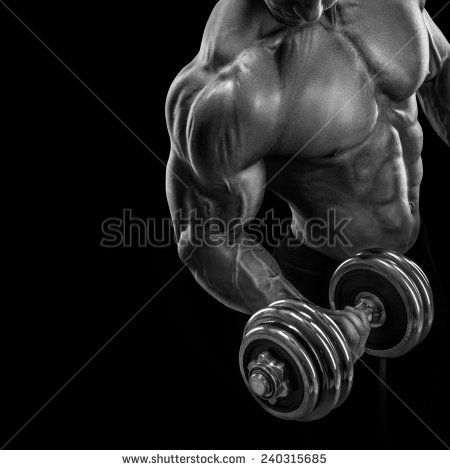 Closeup of a handsome power athletic guy male bodybuilder doing exercises with dumbbell. Fitness muscular body on dark background.Black and white photo