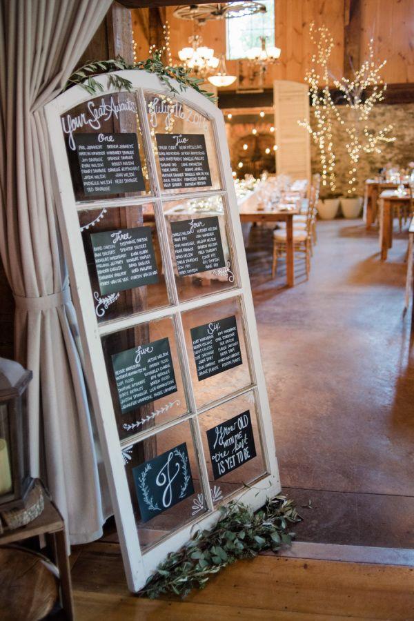 Rustic glass wooden framed door escort card display: http://www.stylemepretty.com/canada-weddings/ontario/jordan-on/2016/11/02/a-rustic-glam-wedding-with-shades-of-blush/ Photography: Karina-Ann - http://karina-anne.com/blog/