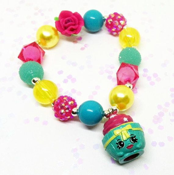 This adorable Shopkins bracelet features Season 3 Cupcake with an assortment of coordinating 12mm acrylic beads and a polymer clay flower bead all double strung with durable stretch floss cord. The bracelet pictured is a childs average (6-10) but I am more than happy to resize it for
