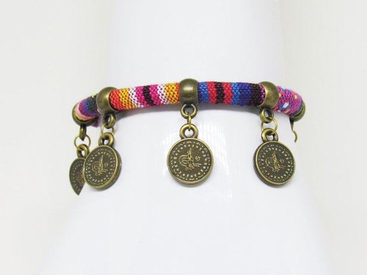 Pulseira Étnica Moedas. Moderna e descontraída, esta pulseira é feita com cordão de poliéster com estampa étnica rosa e roxo e detalhes em ouro velho.