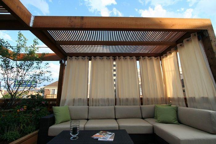 Простая, но симпатичная пергола украшена милыми шторами, которые создают невероятно комфортную обстановку.