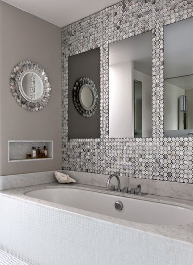 gray tinted pearl bath. A pearl and abalone mirror, hangs above an alcove in Carrara marble in which are laid some pretty perfume bottles, creating light effects on the iridescent surfaces. The tub wall is covered with Bisazza glass mosaic tiles and Vola taps, complementing the refinement of décor with a touch of white.