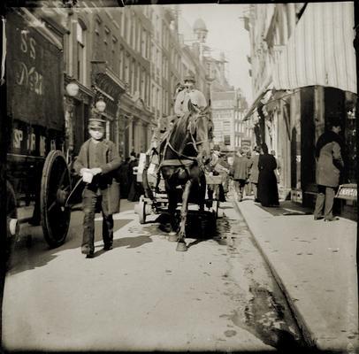 Paard en wagen in de Kalverstraat bij het Spui. Links de huizen 174, 172, 170 enz. (v.l.n.r.) en rechts de uitgebouwde etalage van nummer 175. voor 1892-1893