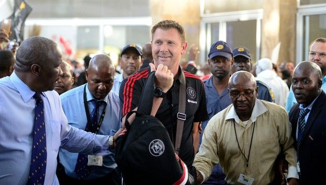 BOSASA RMS Directors Sylvester Simelane tries to get Orlando Pirates coach Eric Tinkler through the crowd at O.R International Airport. The Orlando Pirates fans filled the airport waiting to cheer for their team after they win 4-3 against Al Ahly in the CAF Confederation Cup.