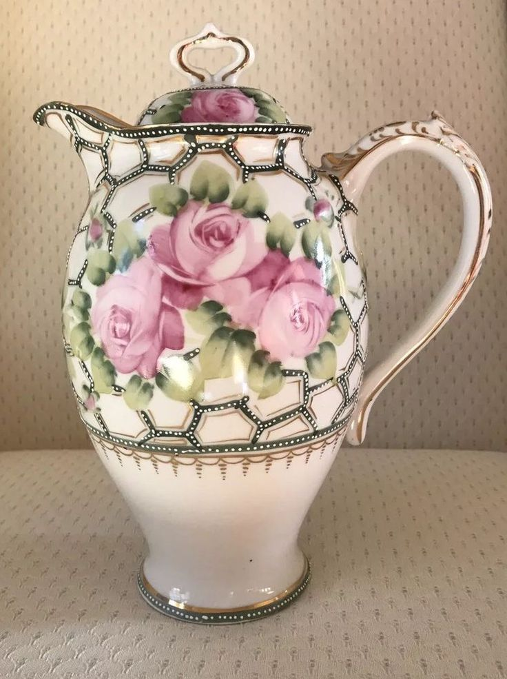 Nippon hand painted porcelain chocolate pot with roses. The mark on the bottom is a maple leaf. Gold gilt.