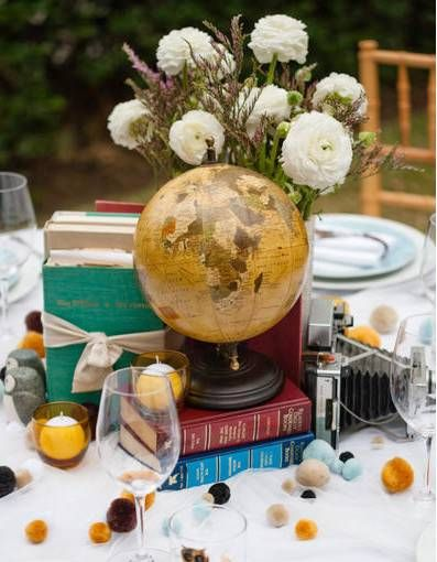 Centerpieces will consist of stacks of vintage books, a mini globe, an antique vase filled with flowers, candles, and worldly souvenirs