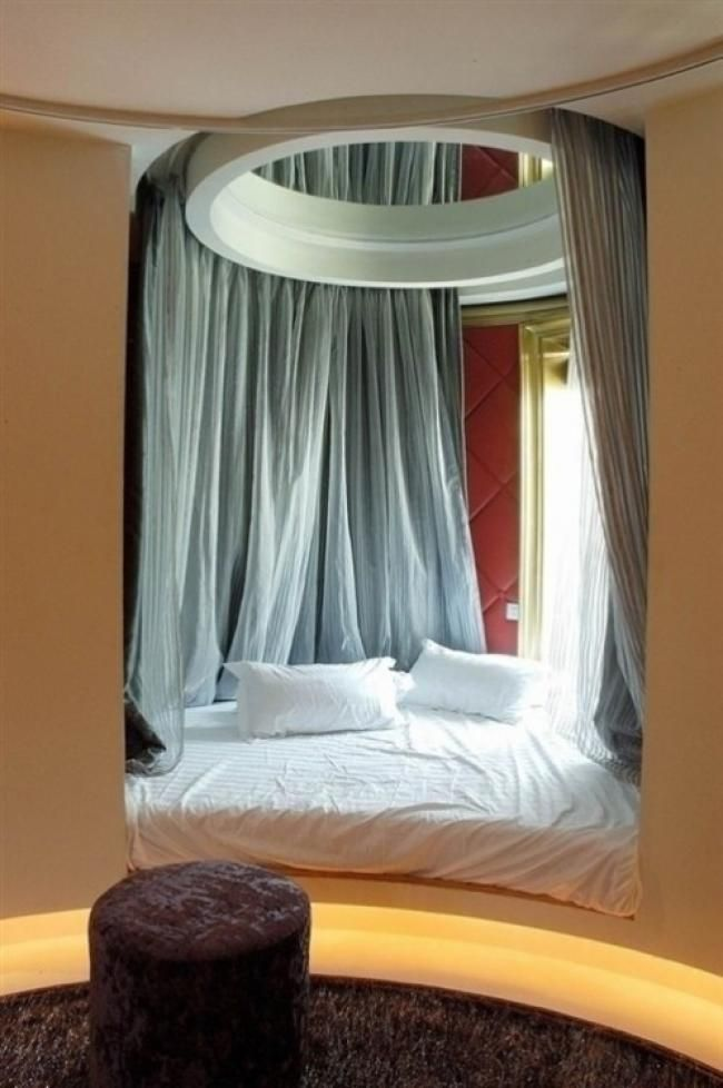 Eclectic bedroom featuring an oversized mirror and an alcove bed