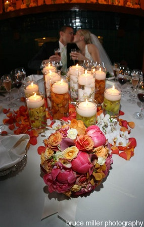 Beautiful centerpiece arrangement affordably done.  Vases, orchids, floating candles, and rose petals.  Brides bouquet laid front and center for a splash of color