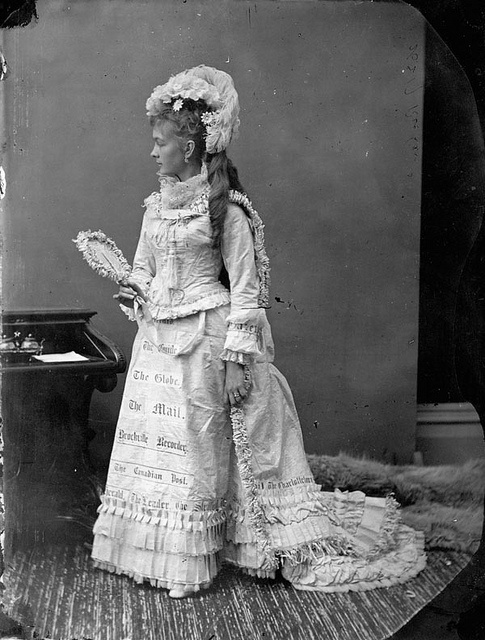 March 1876: a Victorian woman identified as Miss Richards wearing a dress with the names of Canadian newspapers on it.