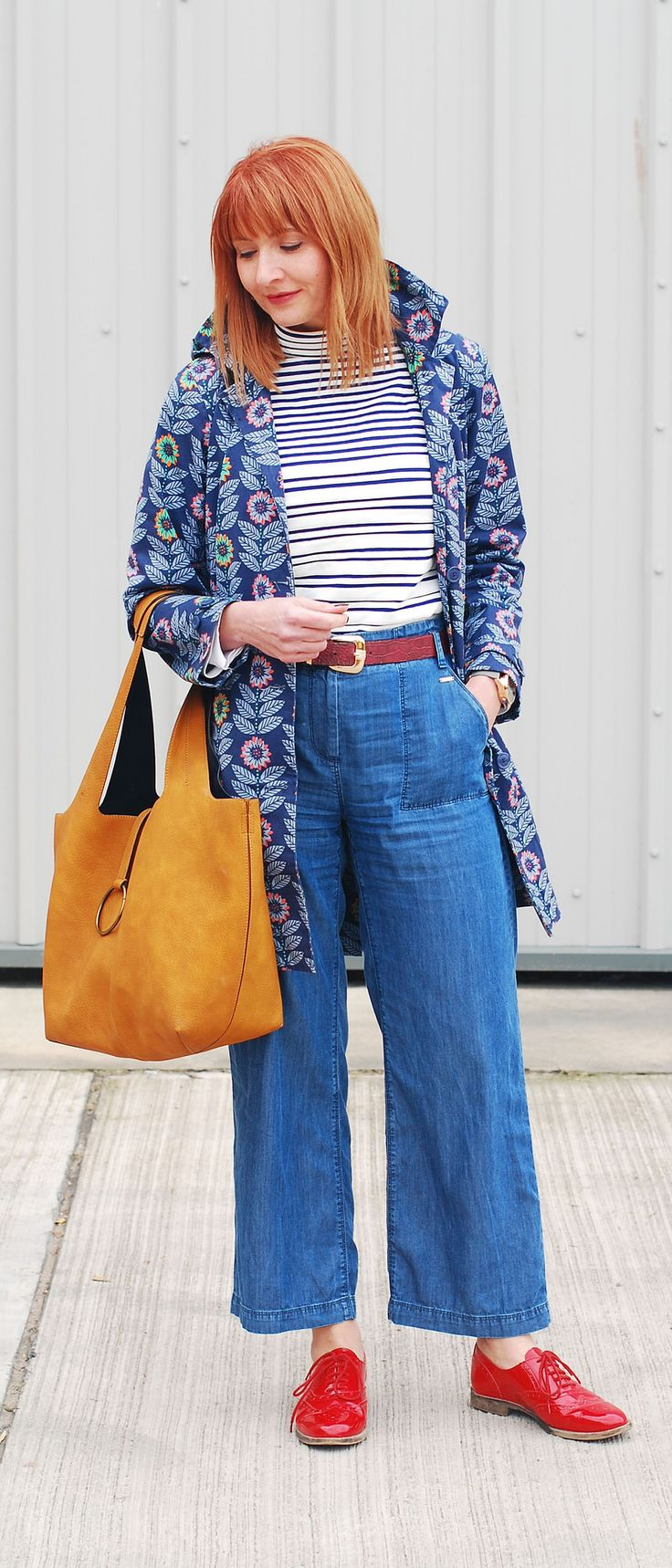 Bright spring weather outfit: Floral Seasalt raincoat  high neck stripe Breton top  wide leg cotton denim trousers  red brogues  ochre bucket bag   Not Dressed As Lamb, over 40 style