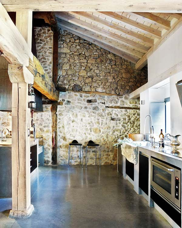 Oh what a feeling - so many elements combined here.. minimalist sleek modern kitchen, unstained raw beams, stone masonry, and concrete flooring..