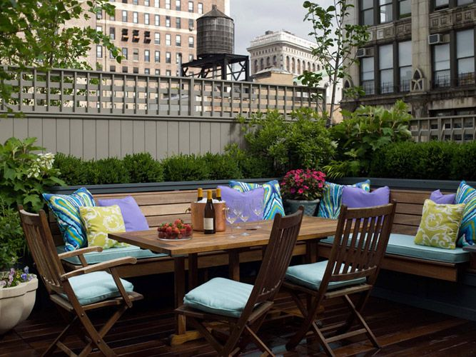 City Roof Top Patio With L Shaped Teak Bench Teak Dining Table Folding Chairs And Purple