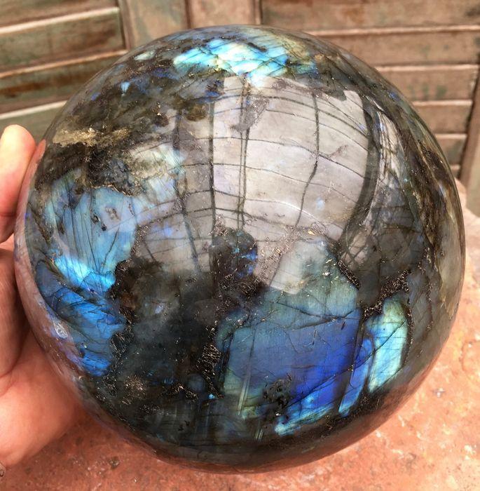 Prachtige grote labradoriet bol met erg mooie iriserende delen. Labradoriet (Spectroliet) is de steen van transformatie (van verandering) en geeft kracht en volharding. Het is een zeer mystieke beschermende steen die het bewustzijn verhoogt.   Diameter: 19,3 cm  Gewicht: 10,48 kg   Wordt aangetekend en verzekerd verzonden.