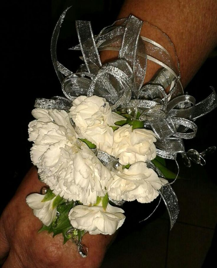 White arm corsage with silver ribbon.