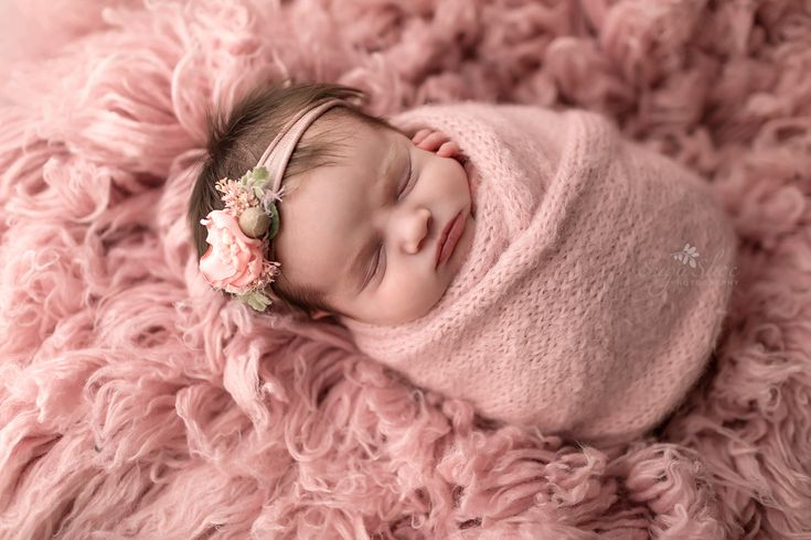Newborn poses baby girl wrapped in pink with a pink floral headband on top of a pink flokati