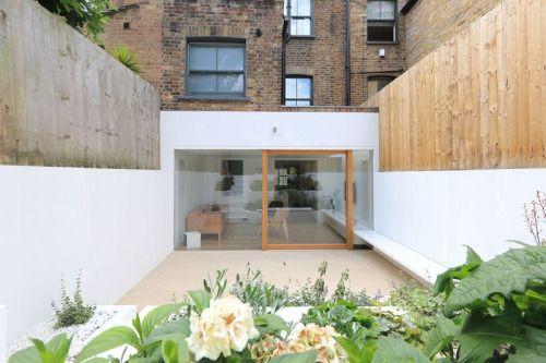 Een uitbouw van de eetkamer in het souterrain is in het ontwerp van Tamir Addadi een ruime kamer geworden met een mooi uitzicht op de terrasvormige tuin.