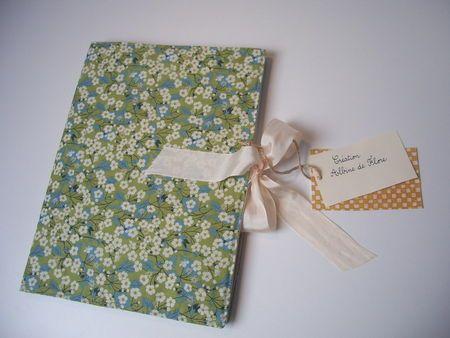 Un tuto pas à pas en photos pour créer une couverture de cahier en tissu. Un petit ruban permet de garder le cahier fermé.