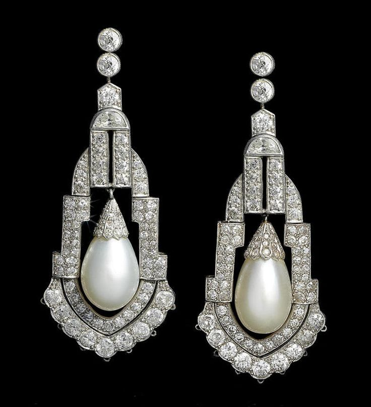 A pair of art deco natural pearl and diamond pendent earrings, circa 1925 Each old brilliant-cut diamond surmount suspending an articulated chandelier pendant, pierced and set with old brilliant, single and rose-cut and half-moon-shaped diamonds, with a central natural pearl drop capped by rose-cut diamonds, mounted in platinum, diamonds approximately 5.40 carats total, later hook fittings, length 5.4cm