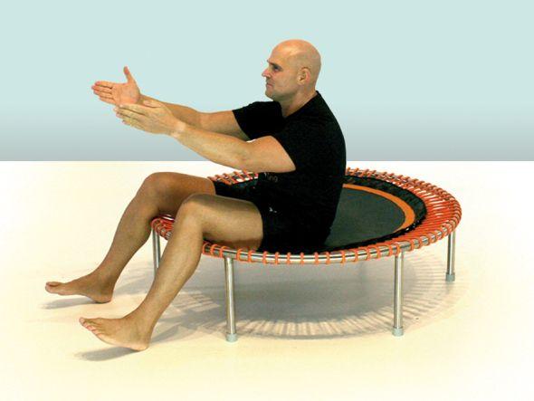 Übung 7  Wenn Ihr jetzt erschöpft seid, bravo - dann habt Ihr Euch richtig angestrengt, ausgepowert und in die Übungen vertieft. Doch die nächste Übung fängt erst an. Setzt Euch dafür in die Mitte des Trampolins und macht Euren Oberkörper richtig rund. Die Füße stehen dabei noch auf dem Boden. Ihr schwingt mit dem Po in die Matte und hebt die Arme vor Euch an. Dann streckt Ihr die Arme von Euch weg, während Ihr mit Eurem Po die Matte in Schwingung versetzt. Spürt Ihr Euren Bauch bzw…