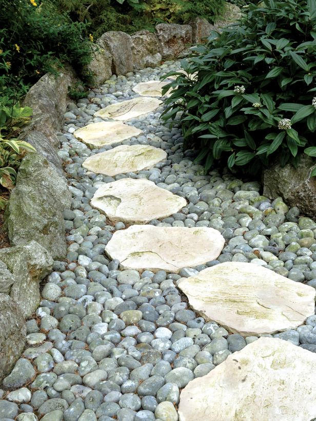 stepping stones carve a path through the landscape with stepping stones bordered by river rock
