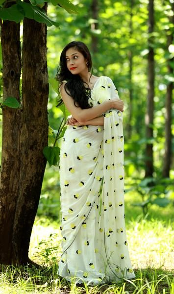 PRODUCT DESCRIPTION: Featuring a white puresilk chiffon saree with windswept yellow crocus flowers embroidered all over, andblack ribbonworksepals and a thin black edging. The sheer white adds thepure, simply sublime, natural grace while the yellow florals add the zest to this breezy, dreamy saree. The yellow flowers are made of embroidered silk threads (two dimensional) and the bottom black leaves are made of ribbon/laces (three dimensional) which together produces a sublime and simple…