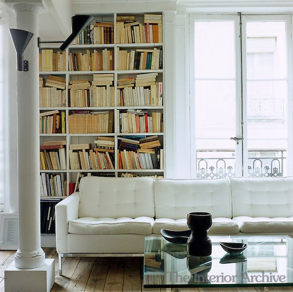 /\ /\ . Frédéric Méchiche . Paris Apartment . Library . A  white leather sofa by Florence Knoll.