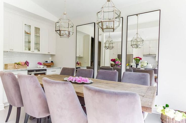 Chic, glam dining room boasts two Suzanne Kasler Morris Lanterns illuminating a salvaged wood dining table lined with purple velvet dining chairs placed before a wall lined with three leaning black framed mirrors.