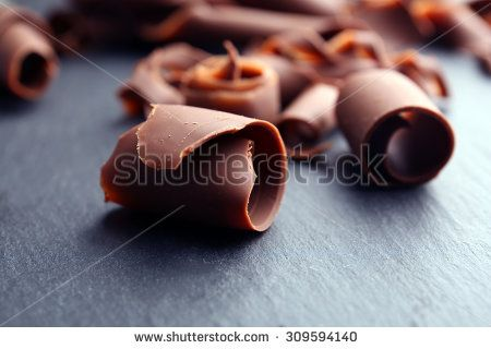 Chocolate curls on wooden table close up - stock photo