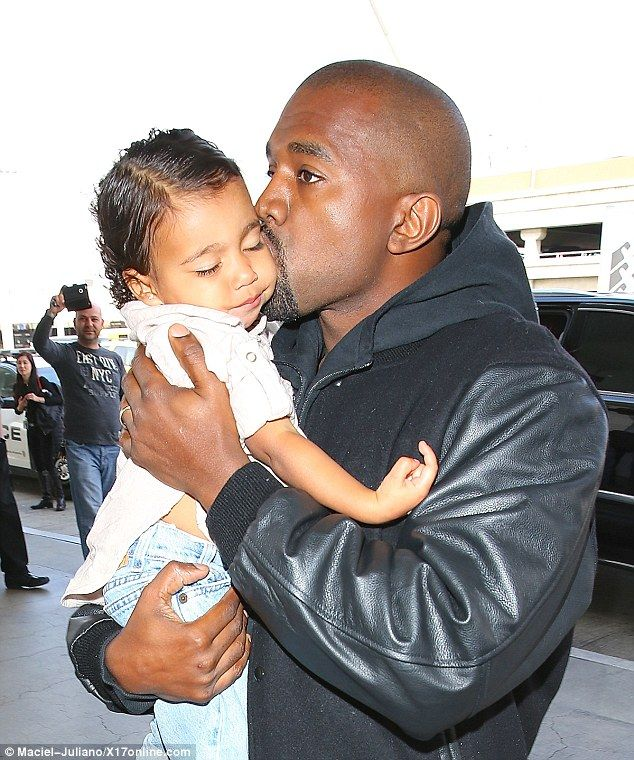 Another look for North: Kanye West gave his little girl a kiss as they arrived at Los Angeles International Airport on Tuesday, as she wore her curly hair slicked back in a centre parting