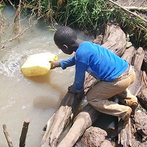A boy gathering dirty water.  Lack of access to clean water is a crisis. Help solve the problems of an entire village by choosing to donate a well to provide clean water. Make a corporate donation or gift in the name of your clients.