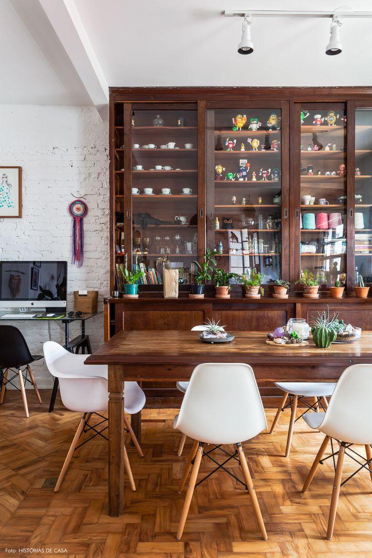 sala de jantar com armário antigo ao fundo, mesa de demolição e cadeiras Eames brancas
