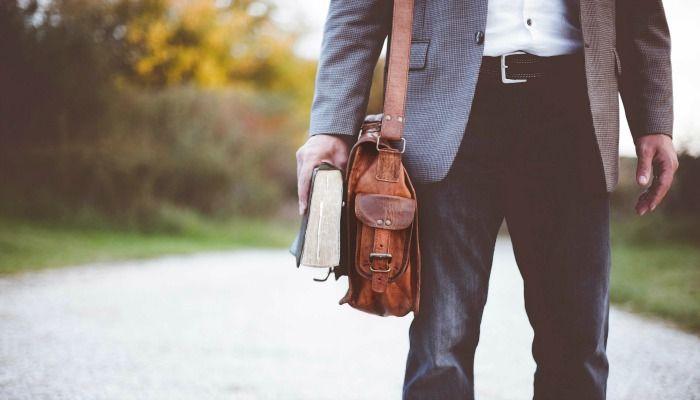 Мужчина в пиджаке держит Священные Писания