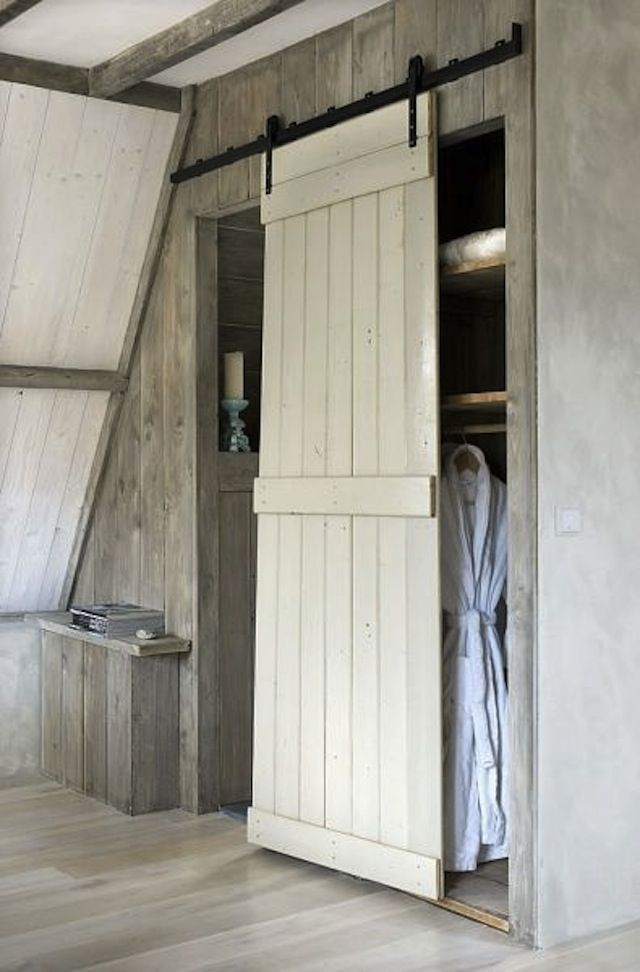 An old barn door functions as both a bathroom and a closet door.