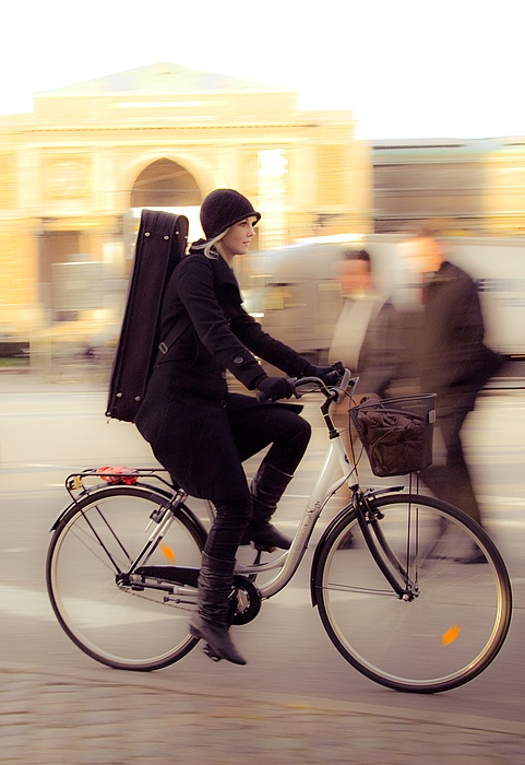 Biking with fashion wool coat, black winter cap and an instrument on her back